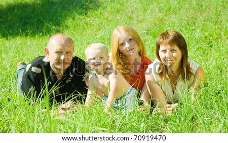 Happy family of 4 people lying on grass under summer sun - stock photo