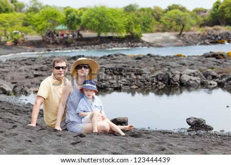 happy family of three at the volcanic black sand beach - stock photo