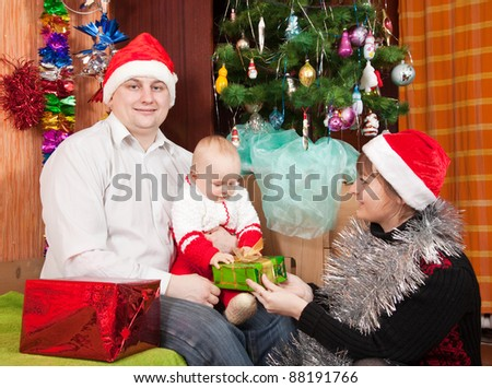 Happy family of three  celebrating Christmas at home
