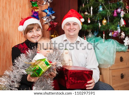 Happy family of three  celebrating Christmas in living room