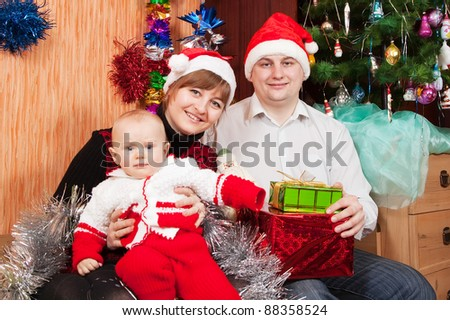 Happy family of three  celebrating Christmas in living room. Focus on man
