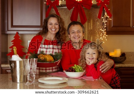 Happy family of three celebrating New Year, Christmas or Thanksgiving day with baked turkey or chicken