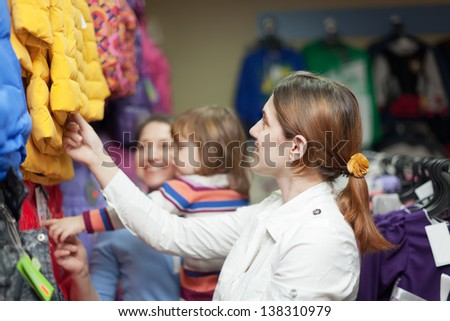 Happy family of three chooses clothes at store