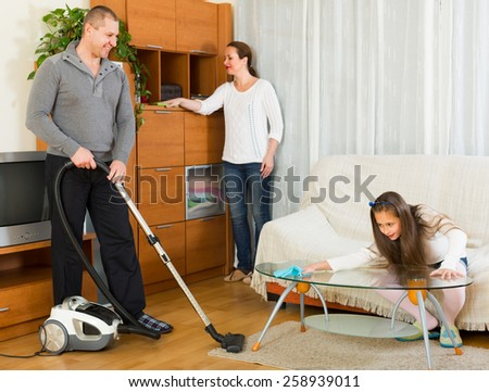 Happy family of three cleaning up a room all together. Focus on man - stock photo