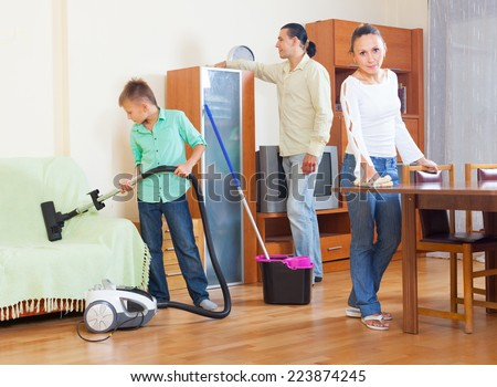Happy family of three cleaning with vacuum cleaner in home
