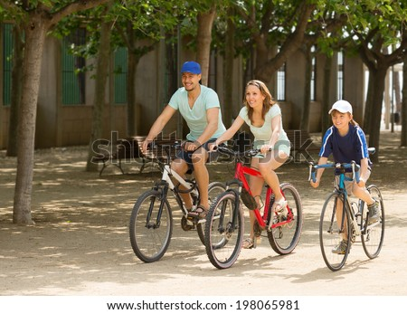 Happy family of three cycling on street road in summer day - stock photo