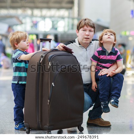 Happy family of three: Father and two little sibling boys at the airport, traveling together. - stock photo