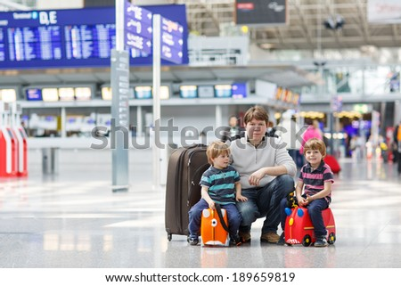 Happy family of three: Father and two little sibling boys at the international big airport, traveling together and going on summer journey. - stock photo