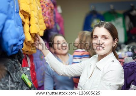 Happy family of three generations chooses jacket at clothes store - stock photo