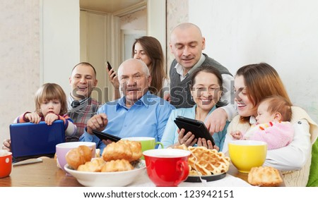 Happy family of three generations or group of friends with electronic devices