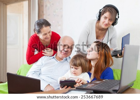Happy family of three generations uses few various electronic devices in home interior