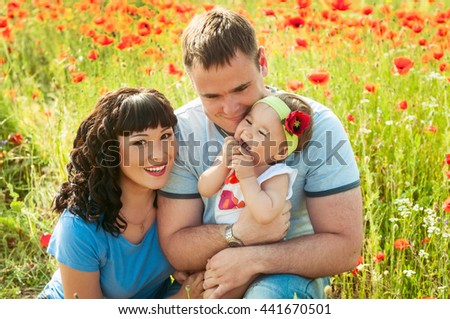 happy family of three having fun and smiling outdoor on the poppy field . Happy young family spending time together outside. Happy mother, father and daughter - stock photo