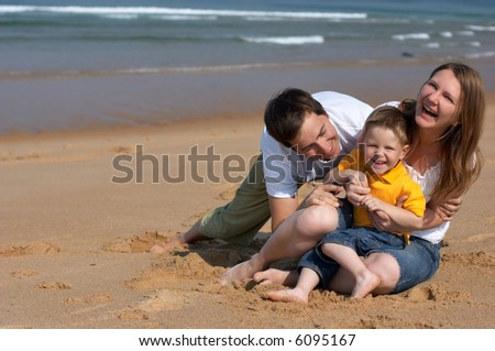 Happy family of three having fun at the beach