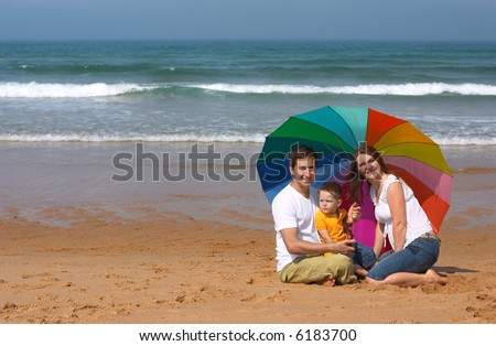 Happy family of three having fun at the beach - stock photo