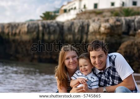 Happy family of three having fun outdoors - stock photo