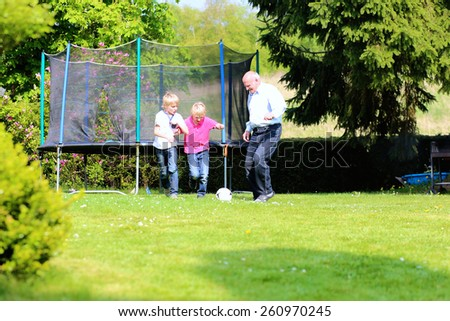 Happy family of three, healthy grandfather with laughing grandsons, twin teenage boys, playing soccer in the garden at the backyard of the house on sunny summer vacation day - stock photo