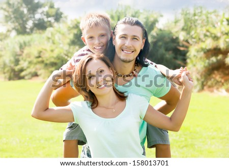 Happy family of three in sunny summer park