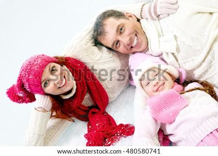 Happy family of three in winter clothing lying on snow and embracing each other