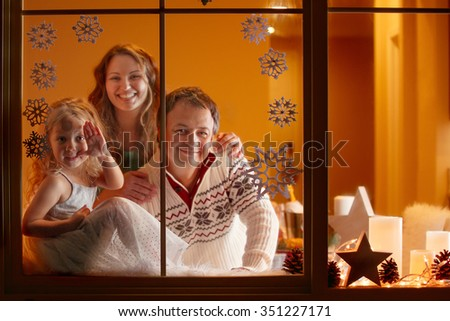 Happy family of three looking through the window at night. Christmas greeting card or cover. - stock photo