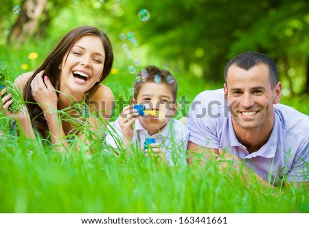 Happy family of three lying on grass while son blows bubbles. Concept of happy family relations and carefree leisure time - stock photo