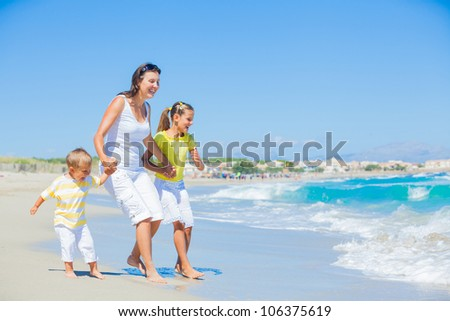 Happy family of three - mother and her child running and having fun on tropical beach - stock photo