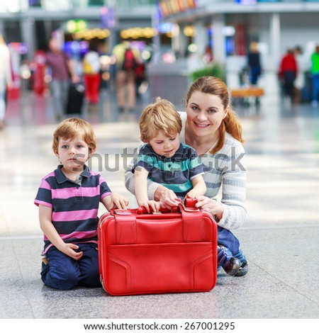 Happy family of three: Mother and two little sibling boys at the airport, traveling together. Little kid boys enjyoing holidays and vacations. - stock photo