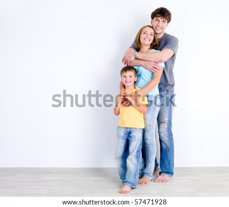 Happy family of three people standing in embrace near the empty wall