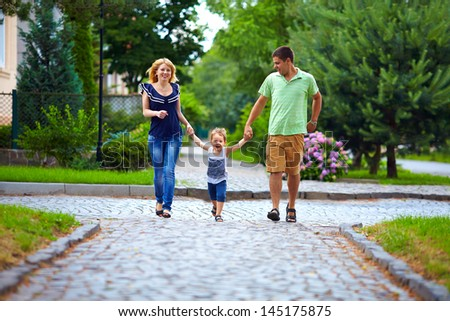 happy family of three persons running the street - stock photo