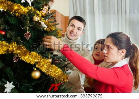 Happy family of three preparing for Christmas - stock photo