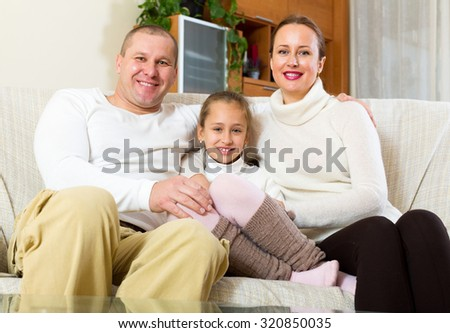 Happy family of three relaxing at home