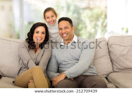 happy family of three relaxing together at home - stock photo