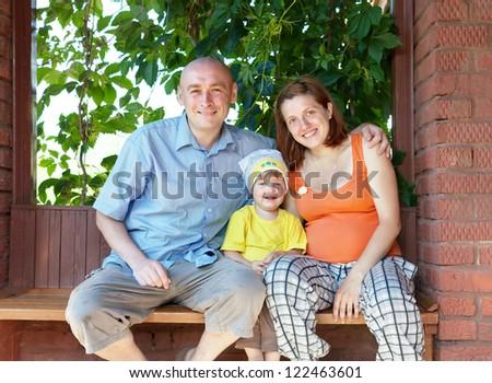Happy family of three sits on bench in veranda - stock photo