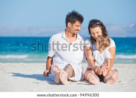Happy family of three sitting and having fun on tropical beach - stock photo