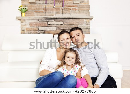 Happy family of three sitting on the couch - stock photo