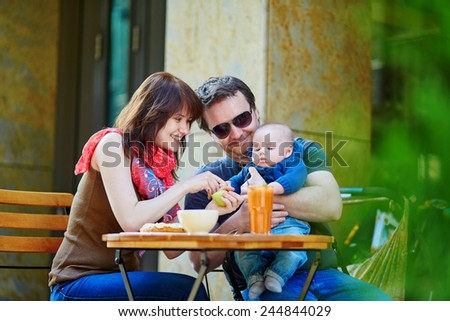 Happy family of three spending their family time together in an outdoor cafe - stock photo