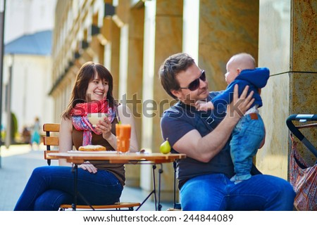 Happy family of three spending time together in an outdoor cafe, father babysitting his son while mother is having rest - stock photo