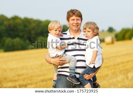Happy family of three: two little twins boys and young father  having fun on yellow hay field in summer - stock photo