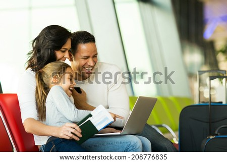 happy family of three using laptop computer at airport - stock photo