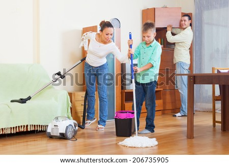 Happy family of three vacuuming together at home