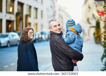 Happy family of three walking together on a street of Paris - stock photo