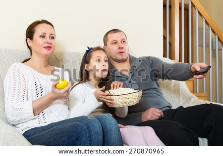 Happy family of three watching movie in domestic interior at home. Focus on girl - stock photo