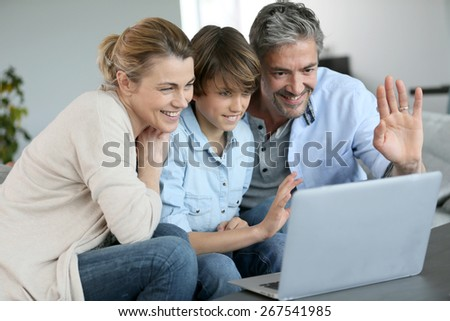 Happy family of three waving at camera during video call - stock photo