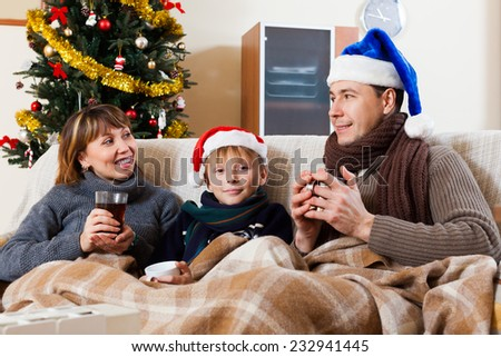 Happy family of three with cups of tea in Christmas time - stock photo