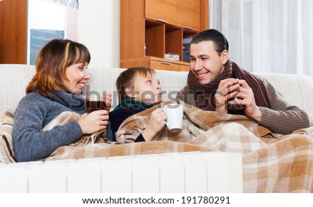 Happy family of three with cups of tea warming near warm radiator in home - stock photo
