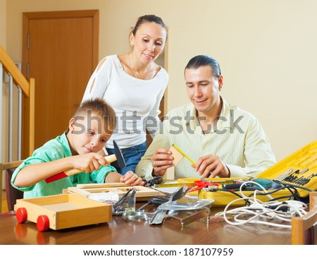Happy family of three with teenager modeling something with instruments - stock photo