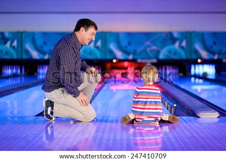 Happy family of two, active father with little daughter, adorable blonde toddler girl, playing bowling together enjoying weekend leisure activity - stock photo