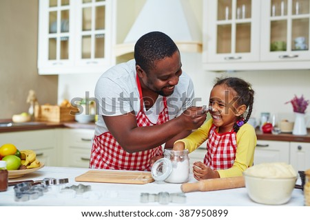 Happy family of two cooking together at home - stock photo