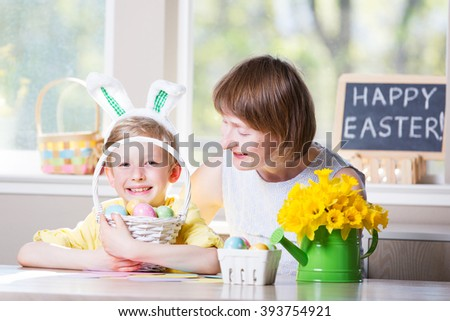 "happy family of two enjoying easter time at home, doing crafts, little boy with bunny ears holding basket with colorful easter eggs, decorations and blackboard sign ""happy easter!"" in the background"