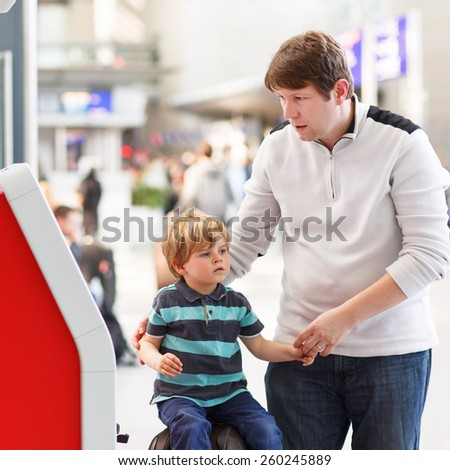 Happy family of two: Father and little son at the airport, traveling together and checking in at terminal. - stock photo