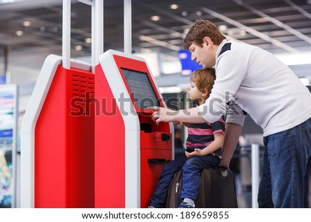 Happy family of two: Father and little son at the international airport, going on journey together and checking in at terminal. - stock photo